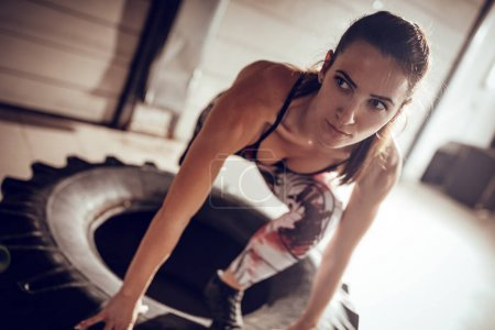 Young muscular woman doing hard exercise on a tire at cross fit training in the garage.