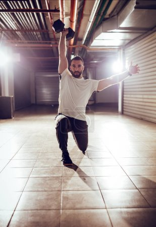 Young muscular man doing overhead lunges exercise with dumbbells on cross fit training at the garage.