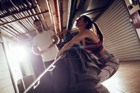 Young muscular woman flipping a tire on cross fit training with personal trainer at the garage.