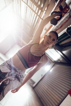 Young muscular woman ready to exercise with kettlebell on cross fit training at the garage.
