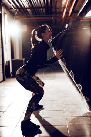 Young muscular woman flipping a tire on cross fit training at the garage.
