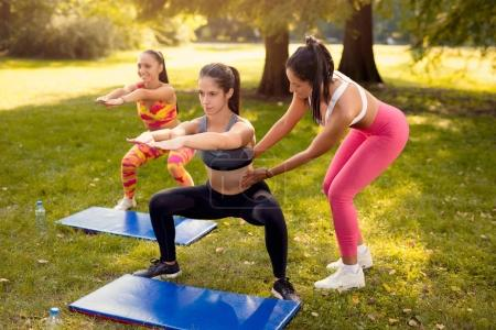 Female personal trainer assisting a beautiful girl doing squats exercise in the park. Selective focus.