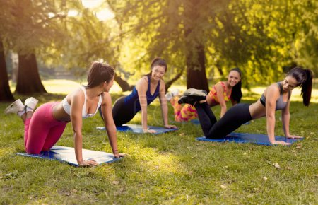 Beautiful girlfriends doing push-up exercise in the park with female fitness trainer. Selective focus.