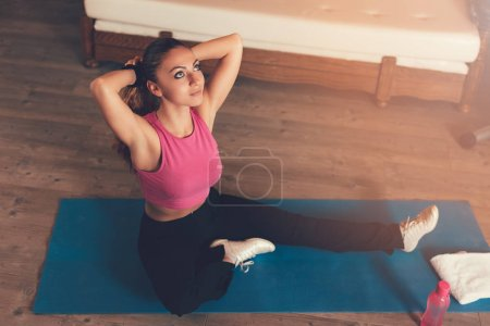 Beautiful girl getting ready for workout at home. She is binds the hair in a ponytail.