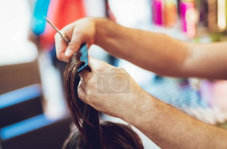 Close-up of a man hairdresser's hands cutting the hair of a woman.