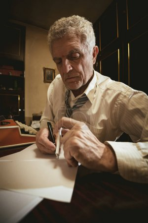 Retro senior man writer with pencil in one and cigarette in the other hand, sitting at the desk and writting some text on the paper.