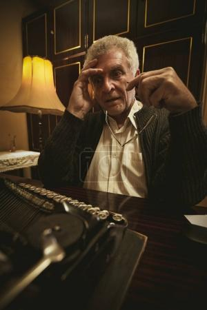 Pensive Retro Senior Man writer with glasses in his hand, sitting at the desk beside Obsolete Typewriter and thinking.