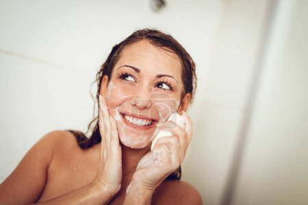 Beautiful young smiling woman washing her face with soap in the bathroom.