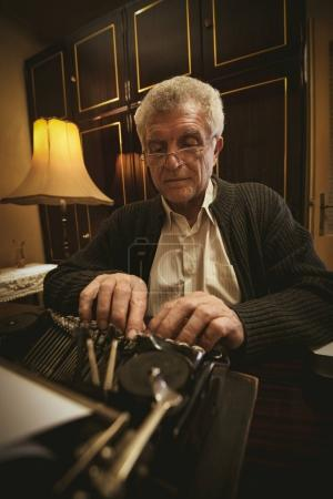 Retro senior man writer with glasses writing on obsolete typewriter.