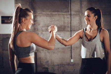 Two young muscular smiling girl celebrating after successful hard workout at the gym.