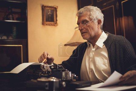 Foto de Escritor de retro hombre alto con gafas y lápiz en la mano sentado en el escritorio y la lectura de algún texto para la escritura en máquina de escribir obsoleta. - Imagen libre de derechos