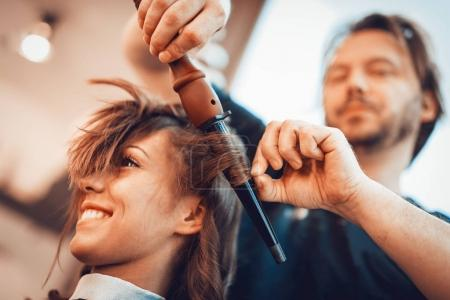 Close-up of a male hairdresser making curls at long brown hair with curling irons.