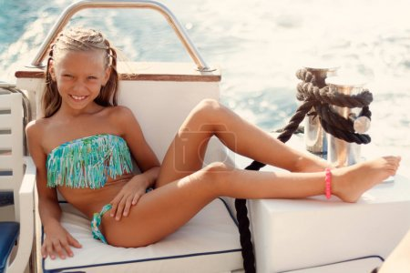 Photo for Cute smiling little girl enjoying on the deck. They are on cruise and sunbathing. - Royalty Free Image