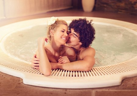 Beautiful young couple enjoying in a hot tub at the spa centre.