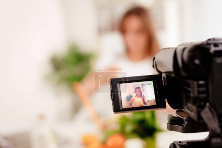 Photo for Beautiful young woman filming her blog broadcast about healthy food at the home. Selectiv focus. Focus on foreground, on camera. - Royalty Free Image