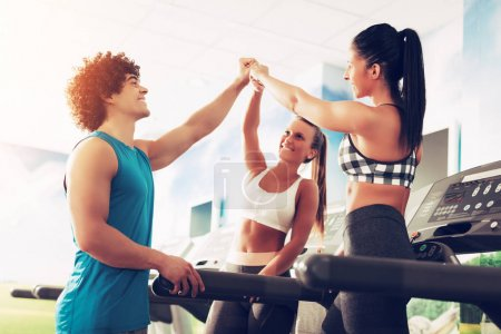 Three happy friends having a sports greeting afther workout at the gym. They are fist bump with smile on their face.