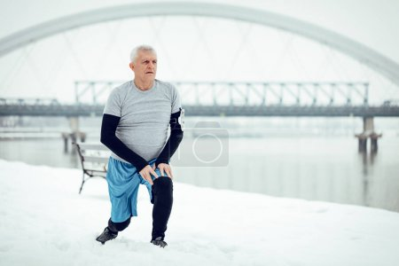 Active senior man stretching and doing exercises by the river during the winter training outside in. Copy space.