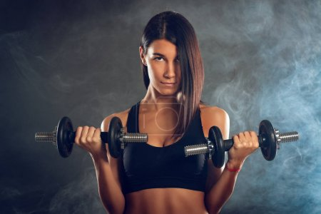 Photo for Attractive muscular young woman doing exercise with dumbbells on dark background. - Royalty Free Image
