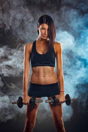 Photo for Attractive muscular young woman standing and holding dumbbell on dark background. She is preparing at doing exercise. - Royalty Free Image
