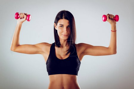 Photo for Attractive muscular young woman doing exercise with dumbbells. - Royalty Free Image