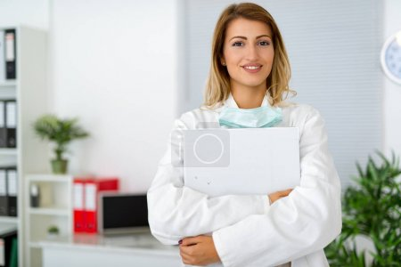 Confident female surgeon holding medical records in clinic office.