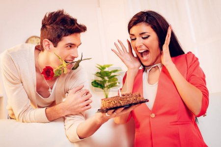 young man with rose in mouth giving birthday cake to woman