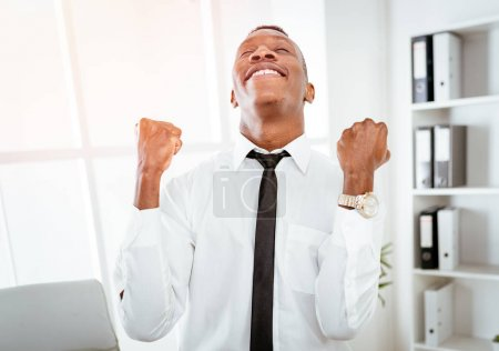 Photo for Successful African businessman celebrating success with raised arms in office - Royalty Free Image
