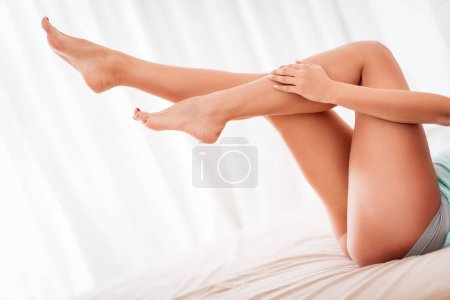 Young woman with legs lying and relaxing on bed at home