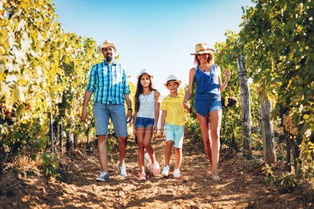 Photo for Beautiful young smiling family of four walking through a vineyard. - Royalty Free Image