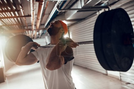 Young muscular man doing high pull exercise with barbell on cross training