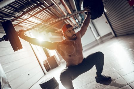 Photo for Young muscular man doing overhead squat exercise with barbell on cross training - Royalty Free Image
