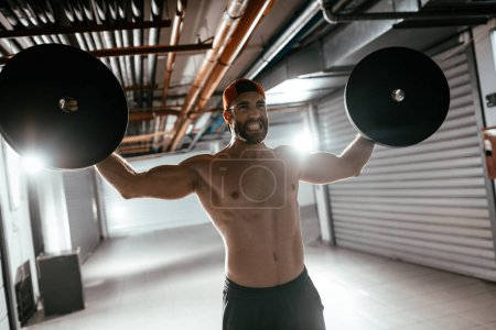 Young muscular man doing hard exercise with weights for shoulders on crossfit training