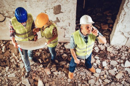 Three construction architects review building and plan reconstruction damaged in disaster