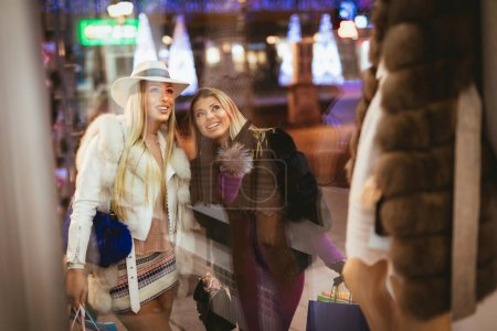 Young women with colorful shopping bags walking in city street at night at Christmas time