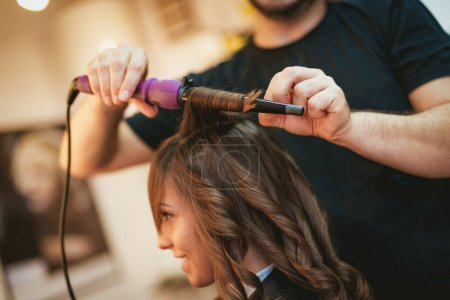 Close view of a male hairdresser making curls at long brown hair with curling irons