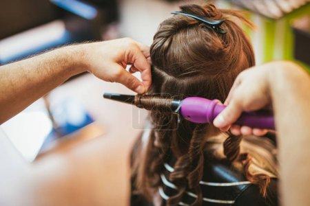 Photo pour Vue rapprochée d'un coiffeur masculin faisant des boucles à de longs cheveux bruns avec des fers à friser - image libre de droit