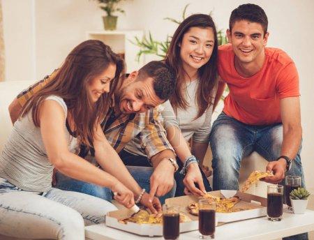 Photo pour Quatre amis joyeux appréciant la pizza ensemble à la fête à la maison - image libre de droit