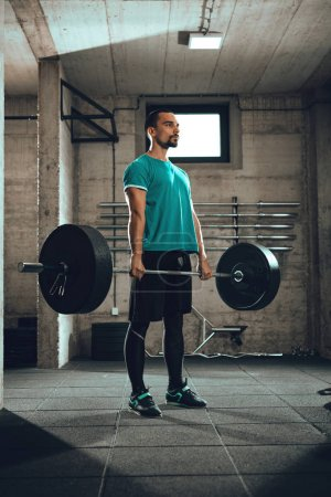 Young muscular man doing deadlift exercise at gym