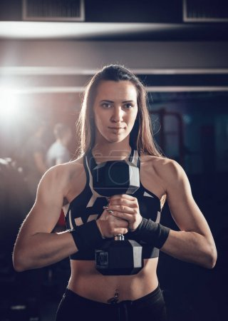 Young muscular woman holding heavy dumbbell in front herself