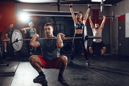 young muscular people doing squat exercise with barbell at gym