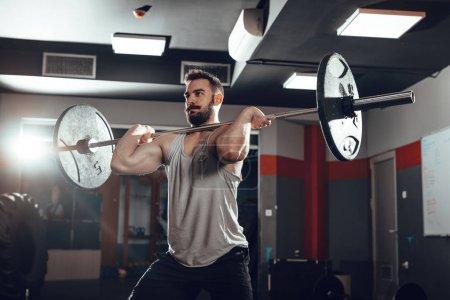 Young muscular man lifting barbell at gym