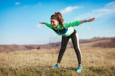 Photo pour Jeune femme de fitness faisant de l'exercice d'étirement après le jogging extérieur - image libre de droit