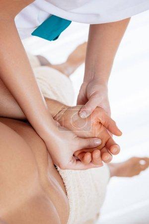 Photo pour Vue rapprochée des mains de jeunes thérapeutes féminines massant de jeunes palmiers mâles dans un spa-salon - image libre de droit