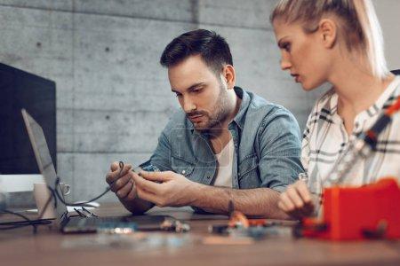 Photo pour Deux jeunes partenaires commerciaux technicien spécialisé dans la réparation d'équipements électroniques - image libre de droit