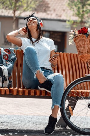 Attractive young woman finds the melody she like best, on the city street, during the stop of riding bike. She is glad of doing this.