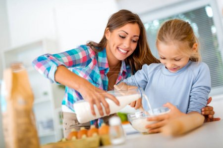 Mother and little girl are pouring the milk in the dish with dough in domestic kitchen. Mother learns her daughter how to make the cookies.