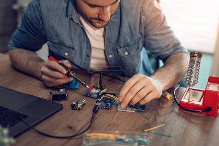 Photo pour Technicien axé sur la réparation des équipements électroniques de fer à souder. - image libre de droit