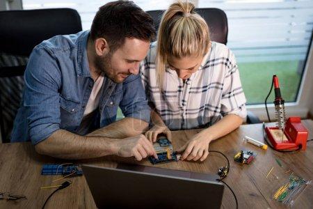 Photo pour Homme à femme brasage d'éléments de circuit imprimé - image libre de droit