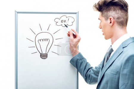 Portrait of young business man having creative idea and drawing light bulb