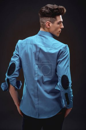 Rear view of handsome fashionable man in turquoise shirt on black background